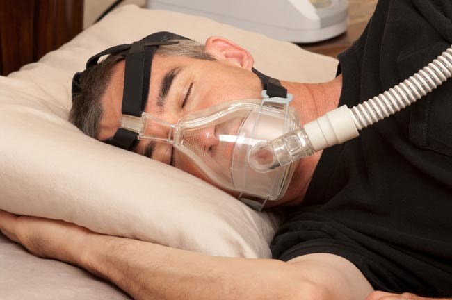Man sleeping while wearing a CPAP machine mask prescribed at South Austin Dental in Austin, TX