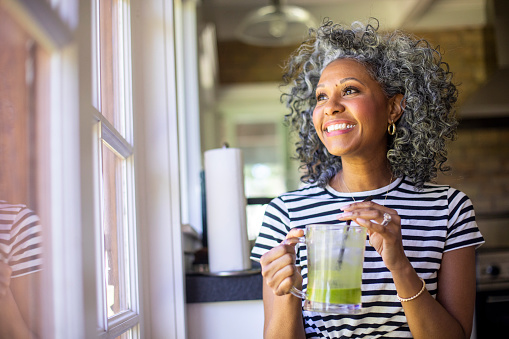 Smiling woman with curly hair enjoying a smoothie